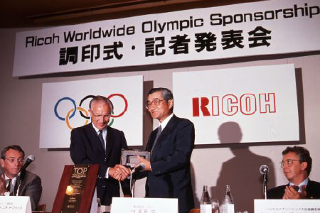 Then IOC President Juan Samaranch and Ricoh President Hamada signed the agreement (at Takanawa Prince Hotel in Tokyo, on September 19, 1989)